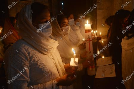 Pakistani Christian worshipers pray and hold candles during an Easter vigil mass at Don Bosco Church in Lahore. Christians around the world are marking of Easter Sunday during Holy Week were Christians observed and celebrated the Easter with special Easter vigil mass prayer ceremonies across Lahore.