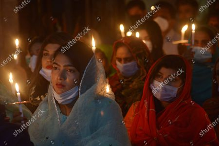 Stock Picture of Pakistani Christian worshipers pray and hold candles during an Easter vigil mass at Don Bosco Church in Lahore. Christians around the world are marking of Easter Sunday during Holy Week were Christians observed and celebrated the Easter with special Easter vigil mass prayer ceremonies across Lahore.