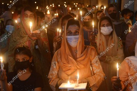Stock Photo of Pakistani Christian worshipers pray and hold candles during an Easter vigil mass at Don Bosco Church in Lahore. Christians around the world are marking of Easter Sunday during Holy Week were Christians observed and celebrated the Easter with special Easter vigil mass prayer ceremonies across Lahore.