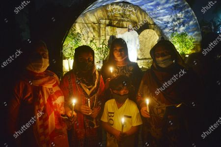 Stock Image of Pakistani Christian worshipers pray and hold candles during an Easter vigil mass at Don Bosco Church in Lahore. Christians around the world are marking of Easter Sunday during Holy Week were Christians observed and celebrated the Easter with special Easter vigil mass prayer ceremonies across Lahore.
