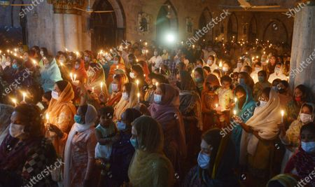 Editorial picture of Christian worshipers pray and hold candles during an Easter vigil mass at Don Bosco Church, Lahore, Punjab, Pakistan - 03 Apr 2021