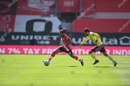 Southampton's Theo Walcott, left, duels for the ball with Burnley's Dwight McNeil during the English Premier League soccer match between Southampton and Burnley at St. Mary's Stadium in Southampton, England