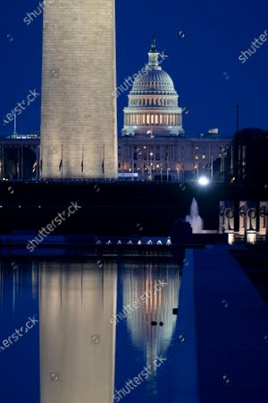 The US Capitol (R) and Washington Monument are seen before dawn in Washington, DC, USA, 04 April 2021. The US Capitol Police Labor Committee is calling for an increase in security following the 02 April attack that resulted in the death of an officer and injury of another. The suspect, identified by law enforcement officials as Noah Green, was shot and killed in the incident.