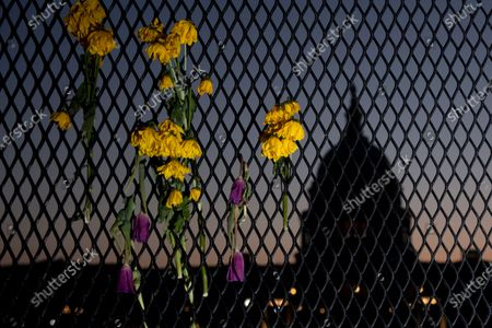 The silhouette of the US Capitol at sunset is seen behind flowers left in a perimeter security fence in Washington, DC, USA, 04 April 2021. The US Capitol Police Labor Committee is calling for an increase in security following the 02 April attack that resulted in the death of Capitol Police Officer William Evans and injury of another officer. The suspect, identified by law enforcement officials as Noah Green, was shot and killed in the incident.