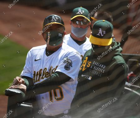 Oakland A's coaches Mike Aldrete (10) and Mark Kotsay (C) watch players enter the dugout before the A's take on the Houston Astros at the Oakland Coliseum in Oakland, California on Saturday, April 3, 2021. The Coliseum requires fans to be masked and socially distance in groups.