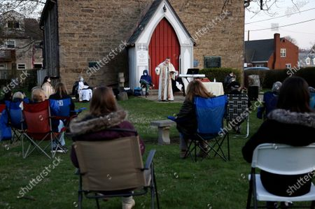 Stock Photo of Congregants of St. Paul's Episcopal church sit on lawn chairs while listening to The Reverend Noah Evans' sermon during an Easter sunrise service held on the burial grounds outside of Old St. Luke's Church in Carnegie, Pa., on . For many congregants, this was the first in-person worship service they have attended since the coronavirus surge in November
