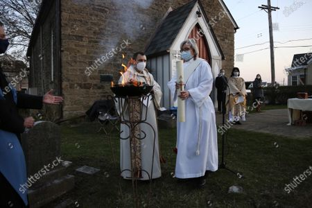 The Reverend Noah Evans helps Deacon Jean Chess light the Paschal candle during St. Paul's Episcopal Church's Easter sunrise service, held on the burial grounds outside of Old St. Luke's Church in Carnegie, Pa., on . For many congregants, this was the first in-person worship service they have attended since the coronavirus surge in November