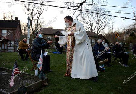 The Reverend Noah Evans of St. Paul's Episcopal Church gives communion to his parishioners, who are scattered throughout the burial grounds of Old St. Luke's Church during their Easter sunrise service, in Carnegie, Pa. For many congregants, this was the first in-person worship service they have attended since the coronavirus surge in November