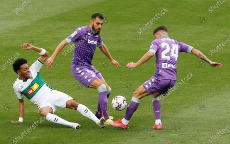 Stock Photo of Elche's Colombian defender Johan Mojica (L) vies for the ball against Betis' striker Borja Iglesias (C) and winger Aitor Ruibal (R) during their Spanish LaLiga soccer match between Elche CF and Real Betis Balompie at Martinez Valero stadium in Elche, eastern Spain, 04 April 2021.