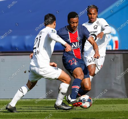 Stock Photo of PSG's defender Abdou Diallo controls the ball sandwiched by Lille's midfielders Benjamin Andre (foreground) and Reinato Luz Sanches (background) during the French L1 football match between Paris-Saint Germain (PSG) and Lille (LOSC) at Parc des Princes Stadium in Paris, FRANCE - 03/04/2021