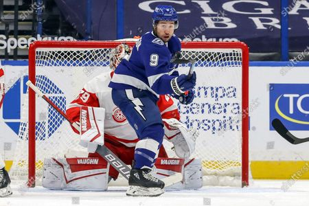 Tampa Bay Lightning's Tyler Johnson controls a high rebound in front of Detroit Red Wings goaltender Thomas Greiss, of Germany, during the first period of an NHL hockey game, in Tampa, Fla