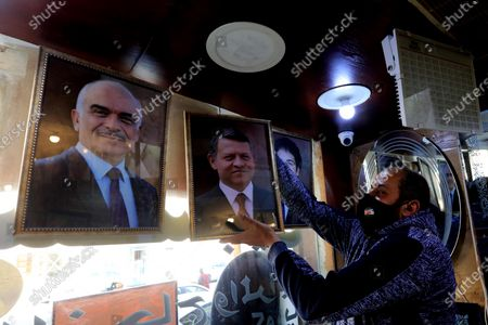 A frame maker in a frameshop hangs pictures of king Abdullah II bin Al-Hussein king of Jordan, in Amman, Jordan, 04 April 2021, a day after several senior figures were detained and the half-brother of King Abdullah II prince Hamzah bin Hussein said that he was put under house arrest. Security agencies, through long-term and comprehensive joint investigations have been following activities and movements by His Royal Highness Prince Hamzah bin Al Hussein and others, said Deputy Prime Minister and Minister of Foreign Affairs and Expatriates Ayman Safadi in a press conference on 04 April.