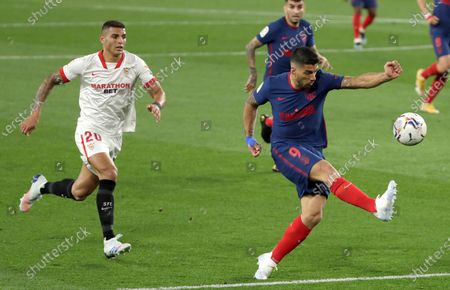 Sevilla's Brazilian defender Diego Carlos (L) and Atletico's Uruguayan striker Luis Suarez (R) in action during the Spanish LaLiga soccer match between Sevilla FC and Atletico de Madrid at Ramon Sanchez Pizjuan stadium in Seville, Andalusia, Spain, 04 April 2021.
