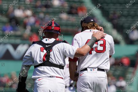 Boston Red Sox's Christian Vazquez (7) places his arm on the shoulder of pitcher Garrett Richards (43) while speaking on the mound during the first inning of a baseball game against the Baltimore Orioles, in Boston. The Orioles won 11-3