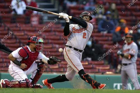 Baltimore Orioles' Freddy Galvis (2) swings at a pitch as Boston Red Sox catcher Christian Vazquez (7) wait for the ball during the ninth inning of a baseball game, in Boston. The Orioles won 11-3
