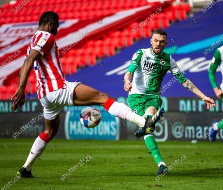 Scott Malone of Millwall crosses the ball past John Obi Mikel of Stoke City; Bet365 Stadium, Stoke, Staffordshire, England; English Football League Championship Football, Stoke City versus Millwall.