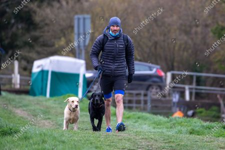 Stock Photo of Picture dated April 3rd shows BBC sports commentator Andrew Cotter with his world famous dogs Mabel and Olive by the River Great Ouse in Ely, Cambridgeshire on Saturday as they prepare for the broadcast of Sunday's Boat Race between Oxford and Cambridge University.