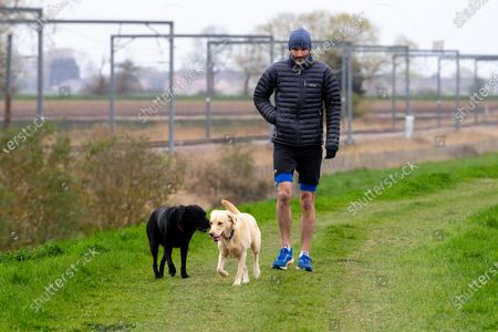 Stock Image of Picture dated April 3rd shows BBC sports commentator Andrew Cotter with his world famous dogs Mabel and Olive by the River Great Ouse in Ely, Cambridgeshire on Saturday as they prepare for the broadcast of Sunday's Boat Race between Oxford and Cambridge University.