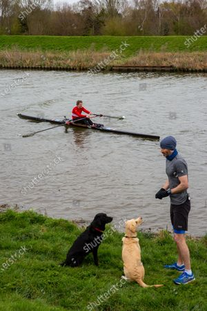 Stock Picture of Picture dated April 3rd shows former Cambridge University rower and Olympian James Cracknell and BBC sports presenter Andrew Cotter with his world famous dogs Mabel and Olive by the River Great Ouse in Ely, Cambridgeshire on Saturday as they prepare for the broadcast of Sunday's Boat Race between Oxford and Cambridge University.