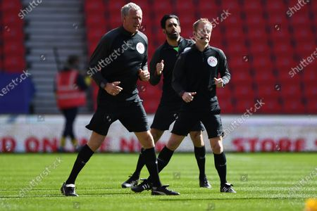 The Officials Assistant Referee Mark Jones Assistant Referee Bhupinder Gill and Referee Gavin Ward warming up during the EFL Sky Bet Championship match between Stoke City and Millwall at the Bet365 Stadium, Stoke-on-Trent