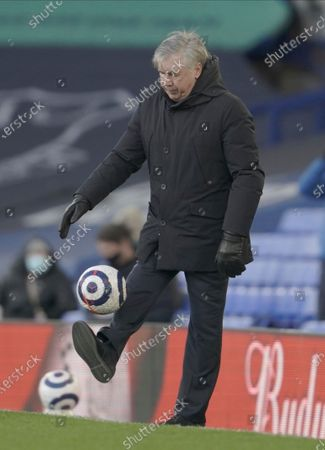 Everton manager Carlo Ancelotti kicks the ball as it comes off of the pitch during the English Premier League soccer match between Everton and Crystal Palace at Goodison Park in Liverpool, England