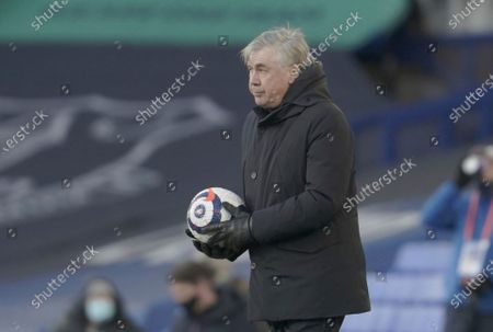 Everton manager Carlo Ancelotti picks the ball up as it comes off of the pitch challenge for the ball during the English Premier League soccer match between Everton and Crystal Palace at Goodison Park in Liverpool, England