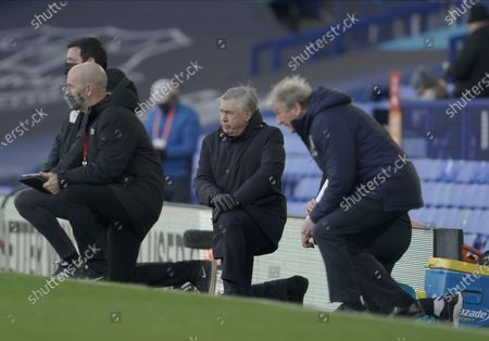 Everton manager Carlo Ancelotti, center, and Crystal Palace manager Roy Hodgson, right, kneel in support of the Black Lives Matter campaign before the English Premier League soccer match between Everton and Crystal Palace at Goodison Park in Liverpool, England