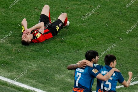Stock Image of Dmitri Tikhiy (top) of Khimki lies on the pitch in pain as Sardar Azmoun (7) and Vyacheslav Karavaev (15) of Zenit Saint Petersburg celebrate a goal during the Russian Premier League match between FC Zenit Saint Petersburg and FC Khimki on April 5, 2021 at Gazprom Arena in Saint Petersburg, Russia.