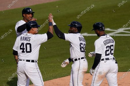 Detroit Tigers' Akil Baddoo (60) is greeted at home plate by Jonathan Schoop, left, Wilson Ramos (40), and Niko Goodrum (28) after his grand slam during the ninth inning of a baseball game against the Minnesota Twins, in Detroit