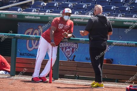Washington Nationals manager Dave Martinez, left, and general manager Mark Rizzo talk during a baseball workout at Nationals Park, in Washington. The Nationals are scheduled to play the Braves on Tuesday