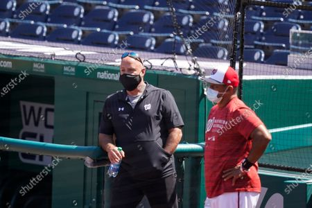 Washington Nationals general manager Mark Rizzo, left, and manager Dave Martinez, watch the team during a baseball workout at Nationals Park, in Washington. The Nationals are scheduled to play the Braves on Tuesday