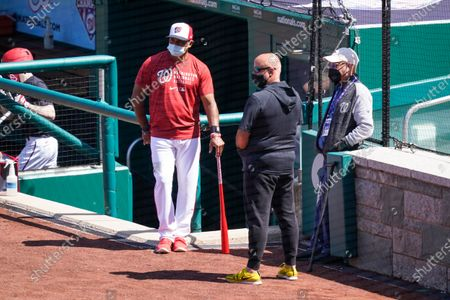 Washington Nationals manager Dave Martinez, left, general manager Mike Rizzo, and owner Mark Lerner watch the team during a baseball workout at Nationals Park, in Washington. The Nationals are scheduled to play the Braves on Tuesday