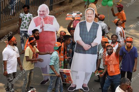 BJP supporters carry cut-outs of Union Home Minister Amit Shah and BJP National President JP Nadda during a roadshow for West Bengal Assembly Election, at Tollygunge on April 5, 2021 in Kolkata, India.