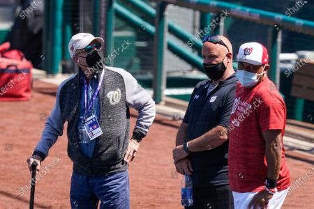Washington Nationals owner Mark Lerner, left, general manager Mark Rizzo, and manager Dave Martinez, watch the team during a baseball workout at Nationals Park, in Washington. The Nationals are scheduled to play the Braves on Tuesday