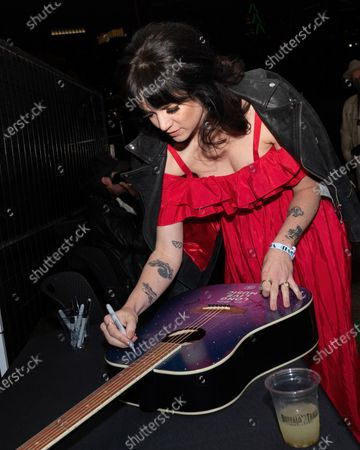 Nikki Lane autographs a guitar during the Long Live Music socially distanced concert event hosted by Luck Reunion and The Long Center