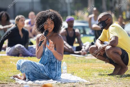 Marley Ralph, left, and cousin Etienne Maurice, right, co-founded the yoga gathering every Sunday at LA High Memorial Park for spiritual healing in the midst of racial and social injustice. The gathering began in June 2020 following the death of Ahmaud Arbery in Georgia in February. Photographed in LA High Memorial Park on Sunday, April 4, 2021 in Los Angeles, CA. (Myung J. Chun / Los Angeles Times)
