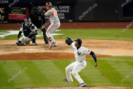 Stock Image of New York Yankees relief pitcher Aroldis Chapman (54) winds up before throwing to Baltimore Orioles Ryan Mountcastle (6) with Yankees catcher Gary Sanchez (24) behind the plate during the ninth inning of a baseball game, at Yankee Stadium in New York. The Yankees shutout the Orioles, handing them their first loss of the 2021 season