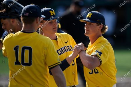 Stock Image of Michigan pitcher Jack White, right, celebrates a strike out with team mates during an NCAA baseball game on Monday 5, 2021, in College Park, Md