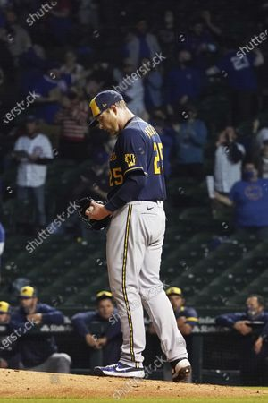 Milwaukee Brewers starting pitcher Brett Anderson looks down after giving up three home runs during the fourth inning of a baseball game, in Chicago