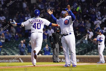 Chicago Cubs' Willson Contreras, left, and third base coach Willie Wilson, right, gesture as he runs the bases after hitting a two-run home run against the Milwaukee Brewers during the fourth inning of a baseball game, in Chicago