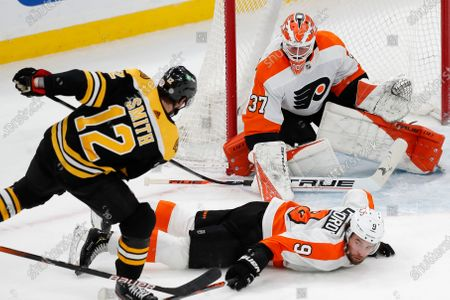 Boston Bruins' Craig Smith (12) shoots on Philadelphia Flyers' Brian Elliott (37) as Ivan Provorov (9) defends during the second period of an NHL hockey game, in Boston