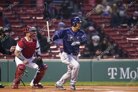 Tampa Bay Rays' Yoshitomo, right, watches the ball on his ground out during the first inning of a baseball game against the Boston Red Sox at Fenway Park, in Boston. At left is Boston Red Sox catcher Christian Vazquez