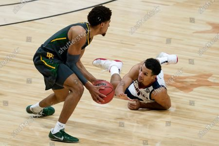 Baylor guard MaCio Teague, left, picks up a loose ball over Gonzaga guard Jalen Suggs, right, during the first half of the championship game in the men's Final Four NCAA college basketball tournament, at Lucas Oil Stadium in Indianapolis