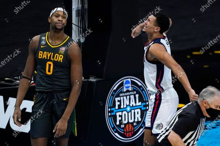 Gonzaga guard Jalen Suggs, right, celebrates in front of Baylor forward Flo Thamba (0) after making a basket during the second half of the championship game in the men's Final Four NCAA college basketball tournament, at Lucas Oil Stadium in Indianapolis