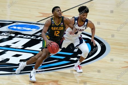 Baylor guard Jared Butler (12) drives up court past Gonzaga guard Aaron Cook (4) during the second half of the championship game in the men's Final Four NCAA college basketball tournament, at Lucas Oil Stadium in Indianapolis