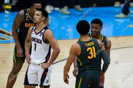 Baylor guard Jared Butler, right, celebrates with teammate guard MaCio Teague (31) in front of Gonzaga guard Jalen Suggs (1) at the end of the championship game in the men's Final Four NCAA college basketball tournament, at Lucas Oil Stadium in Indianapolis