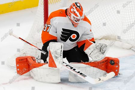 Philadelphia Flyers' Brian Elliott blocks a shot during the second period of an NHL hockey game against the Boston Bruins, in Boston