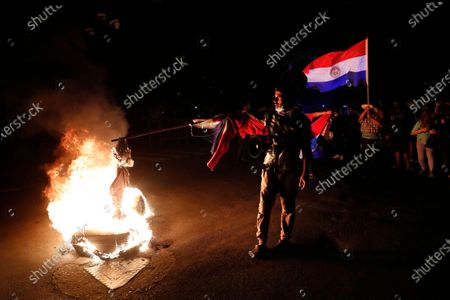 Man burns an effigy during a protest in front of the Congress building, asking for the resignation of President Mario Abdo Benitez over his handling of the coronavirus pandemic and the state of the public health system, in Asuncion, Paraguay