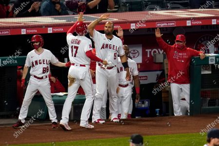 Los Angeles Angels' Shohei Ohtani (17) is met in the dugout by Albert Pujols (5) after Ohtani scored on a fielder's choice during the eighth inning of a baseball game against the Houston Astros, in Anaheim, Calif
