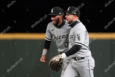 Chicago White Sox right fielder Billy Hamilton, left, is greeted by second baseman Nick Madrigal, right, after Hamilton caught a pop fly hit by Seattle Mariners' J.P. Crawford in the ninth inning to end the baseball game, in Seattle. The White Sox won 6-0